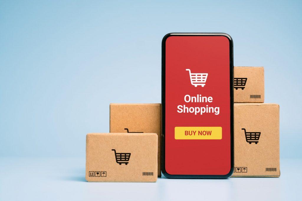 Tra i pacchi, uno smartphone che mostra l'interfaccia di acquisto