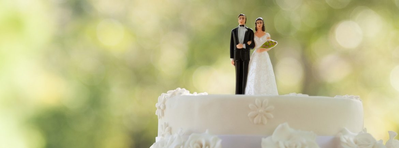 Una coppia di novelli sposi in cima a una torta nuziale