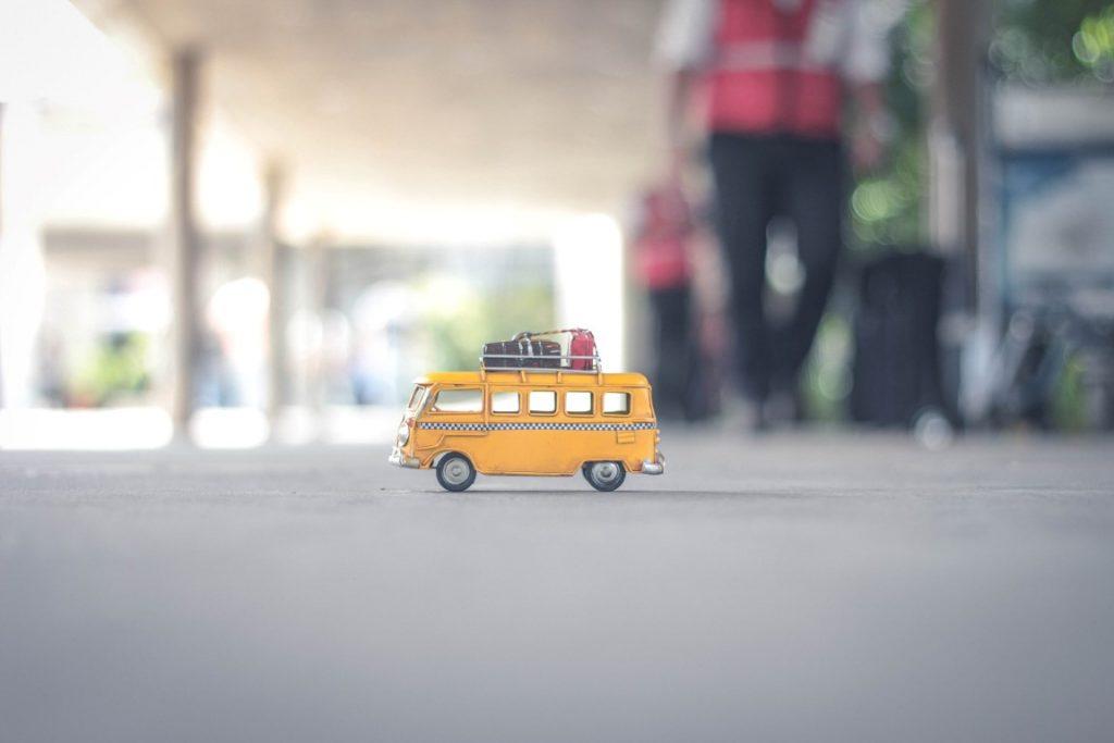 Un pulmino giocattolo giallo sulla strada in mezzo ai passanti.