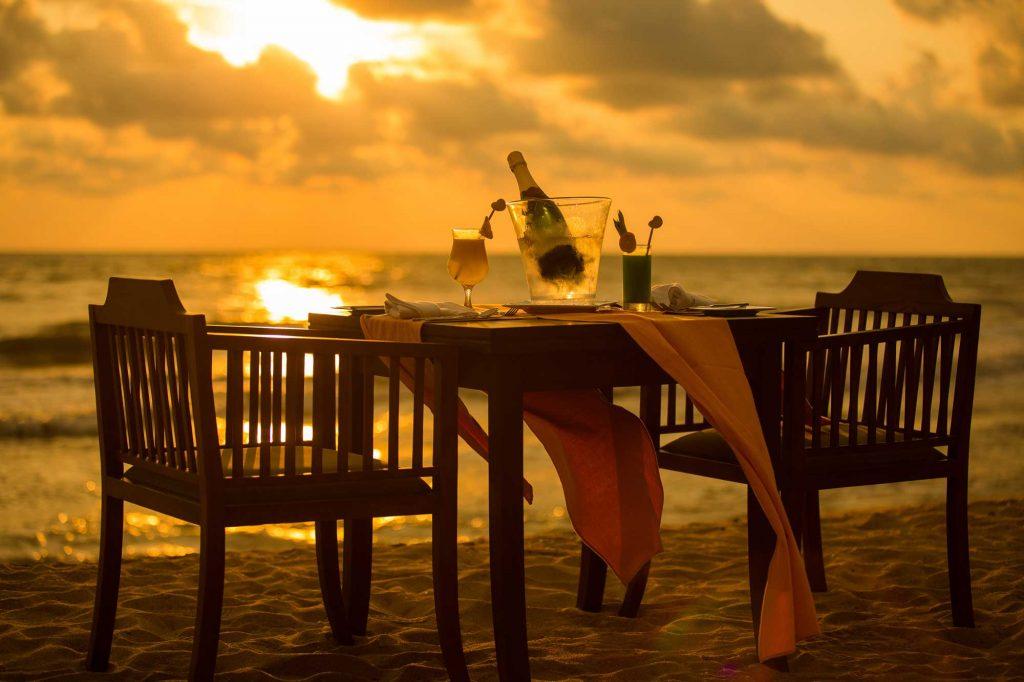 Una bottiglia messa in fresco per su un tavolo per due in riva la mare.