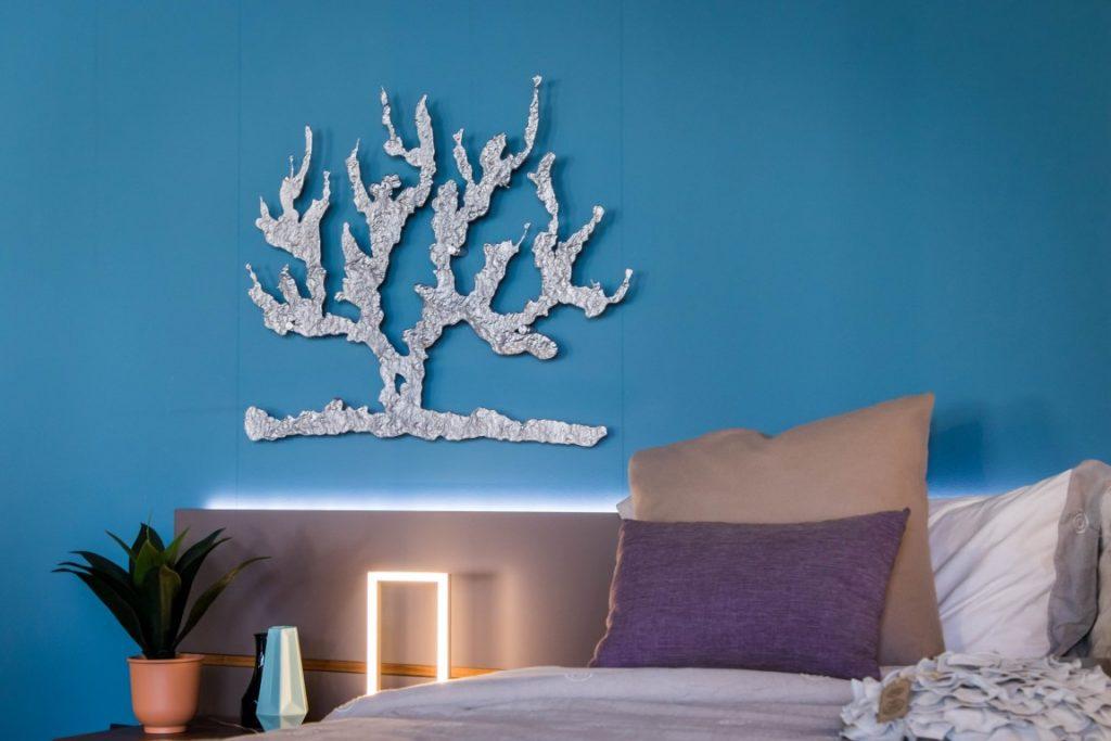 Una scultura metallica da parete appesa in una camera da letto.
