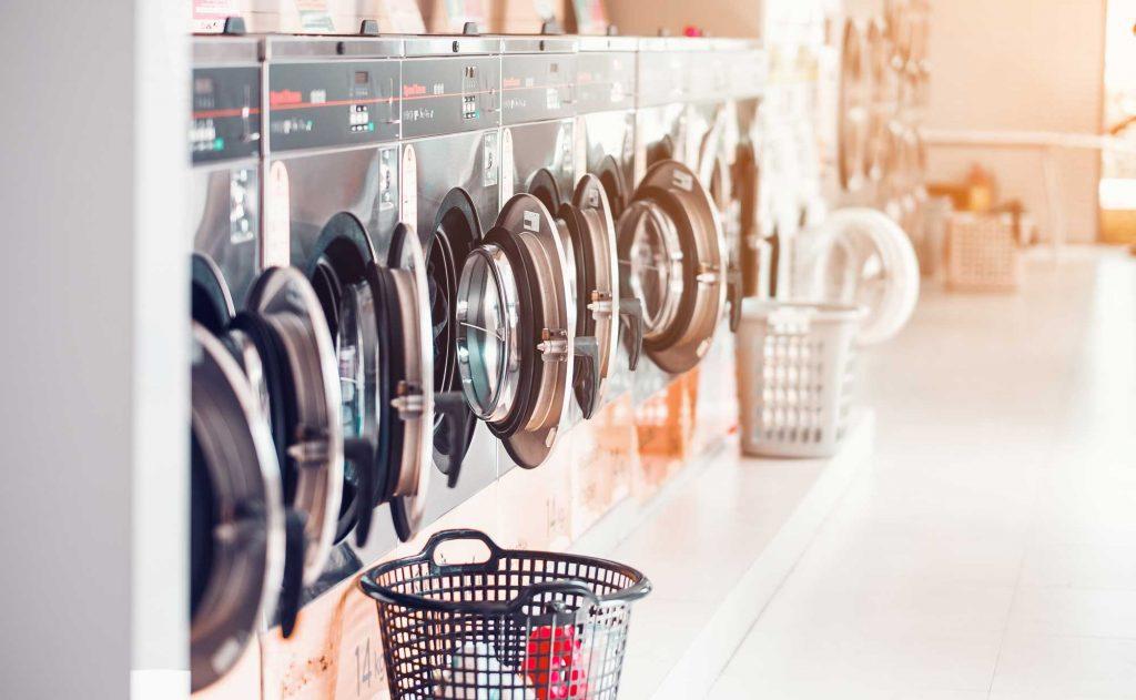 In una lavanderia, una serie di lavatrici con l'oblò aperto
