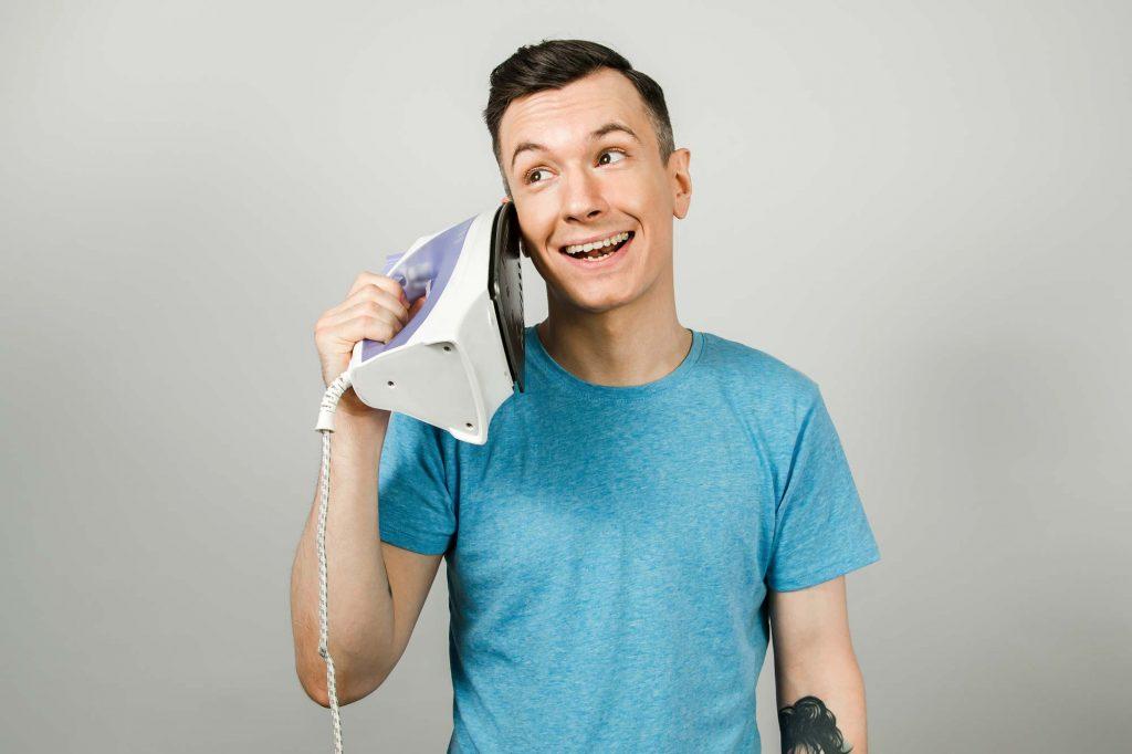 Una ragazzo usa il ferro da stiro come un telefono