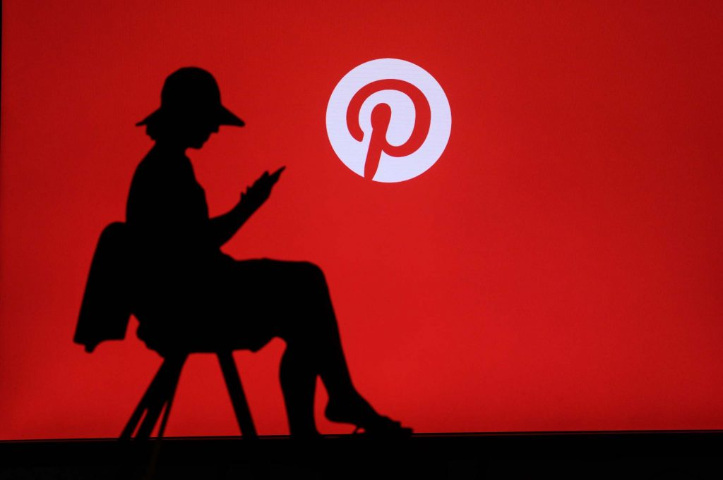 Una donna seduta naviga su Internet dal suo smartphone, sullo sfondo il logo di Pinterest