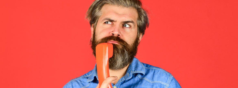 Un uomo perplesso con una cornetta del telefono in mano
